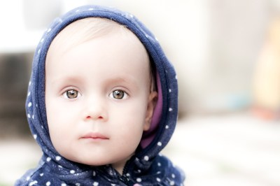 Baby girl with big brown eyes and a hoody.