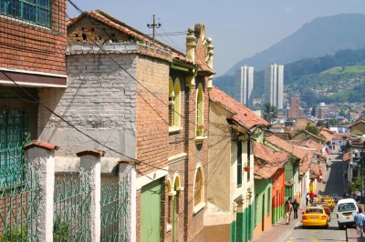 Hilltop view of Candelabra neighborhood in Bogotá, Colombia. Colorful, with taxis, pedestrians, two towers and the Andes mountains.
