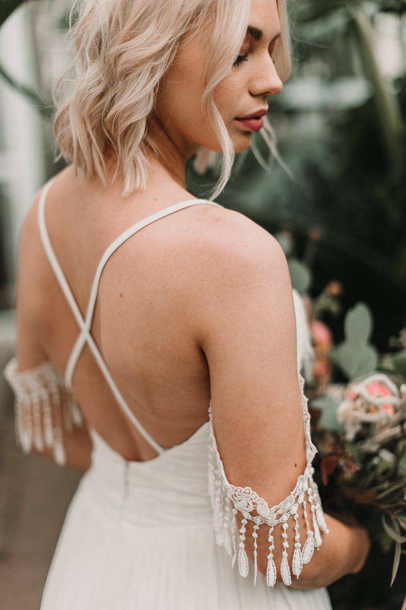 Cross back dress from Shikoba Bride with stunning tassel details. Blush and green Bohemian Wedding Inspiration bringing a little California to you where ever you are in the world. Relaxed styling and desert inspiration and vibes. Wedding ideas for boho brides who an effortlessly relaxed, bohemian wedding. Shot by Natalie Pluck Photography. See full blog post for credits and more inspiration here http://www.nataliepluck.com/bohemian-wedding-inspiration/ 