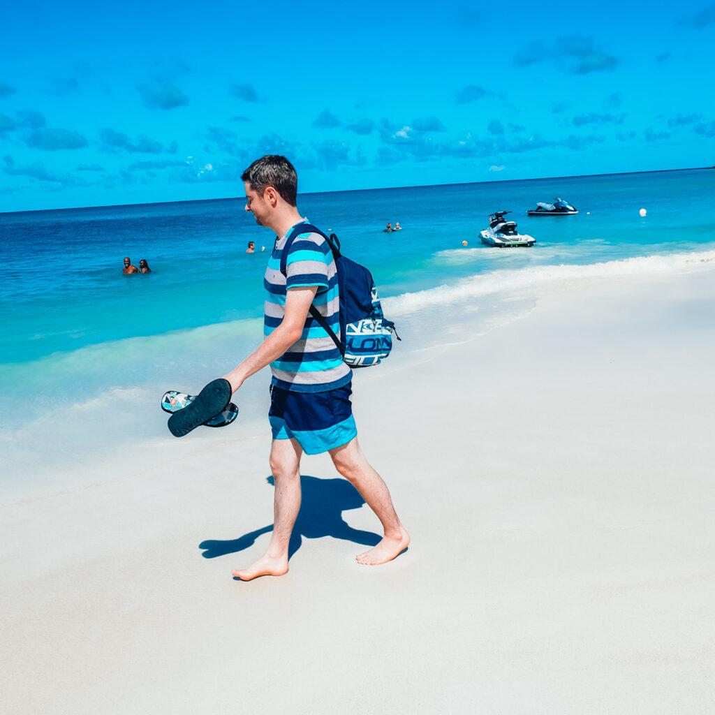 Lee walking along Dickenson Bay Beach in Antigua