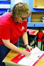 Pamela Weems, principal of Oasis and 7-high school teacher, fills the student's folders with assignments for the first few days of school.