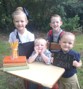 "All ready and smiling for their first day of school is the Strahan family of Silsbee, Texas. Back row is Ella, who is now in the third grade, Cole is in the first grade, sitting is Alden who is now in nursery school and proudly holding the sign with ""2017-2018"" on it is Emma, who is in Pre K 4. All attend the Word of Life Christian School in Silsbee, Texas. Parents are Adam and Amy Strahan and grandparents are Steven and Laura Strahan of Marthaville and Homer and Annette Withers of Pleasant Hill."