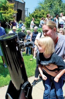 Myranda and Paisley Adkins view the eclipse Aug. 21 at the Natchitoches Parish Library though a special telescope. Photo by Ashley Froust