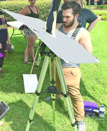 Taylor Dick observes the eclipse at the tent at the CAPA fountain.