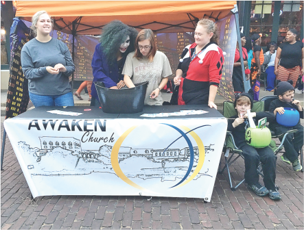 From left are Andi Gillespie, KD Escobedo, Hannah Keck and Shelly Nelson passing out candy at the Awaken Church booth during Witch Way to Main Street.