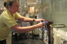 Customer Beth Cole opens a door for her prize. She received another entry into the daily door prize drawing.