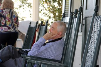 Tommy Whitehead sits in a rocking chair on the front porch.