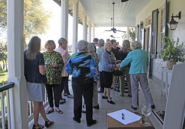 Garden Club members and guests visit on the front porch of the plantation house.