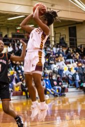 Constaga Thomas, #14, takes a jump shot in the paint for two.