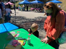 Kelly West and son Nolan participate in activities at a booth