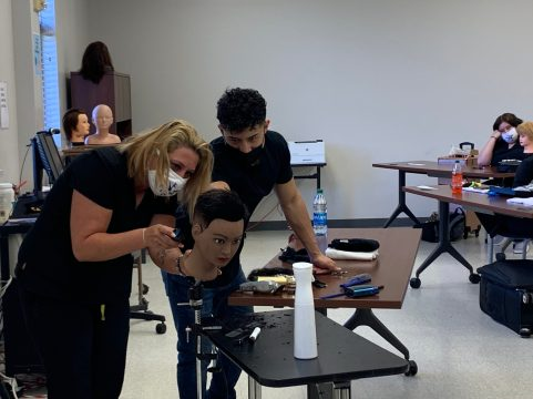 Jorge Arellano watches over student Emilee Smith as she works on the mannequin head.