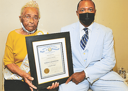 Director of Intergovernmental Affairs Roderick Scott, right, presented Mrs. Norien with a certificate celebrating her amazing milestone.