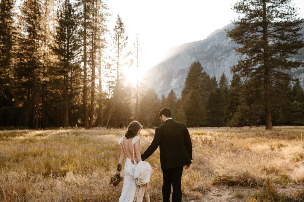Couple walks through Yosemite Valley field