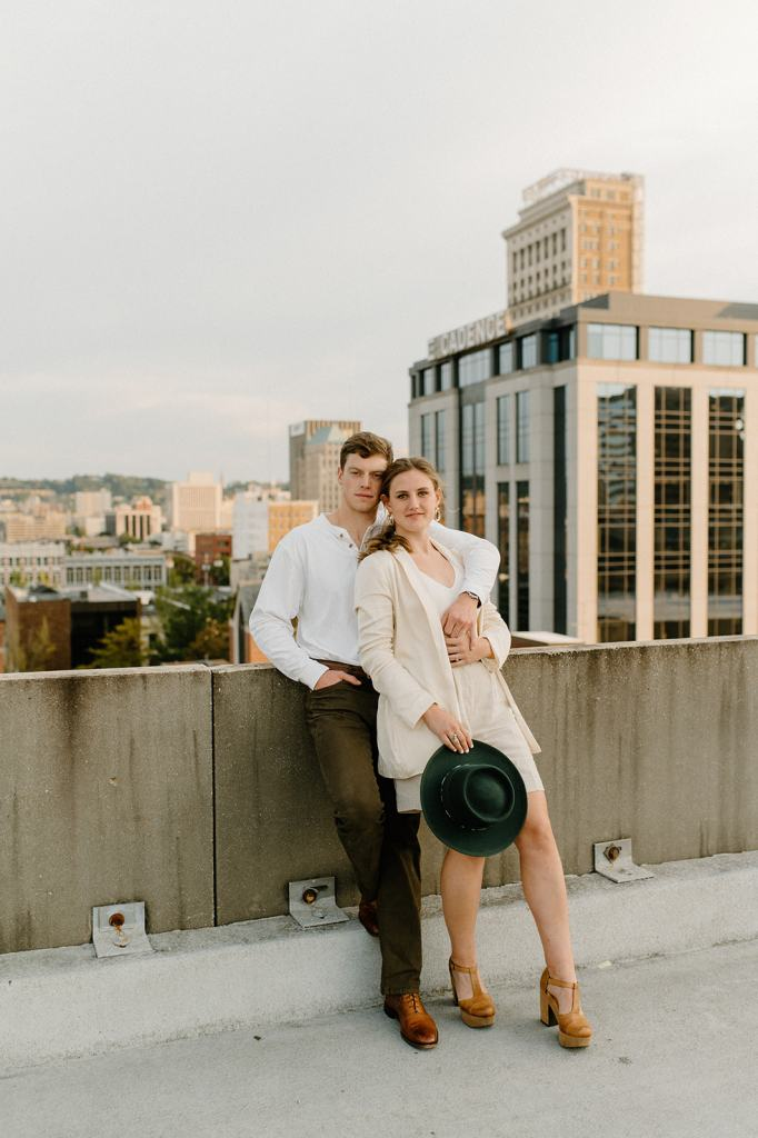 Couple embraces overlooking city at engagement session