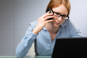 A young female business manager behind a computer talks on a mobile phone.