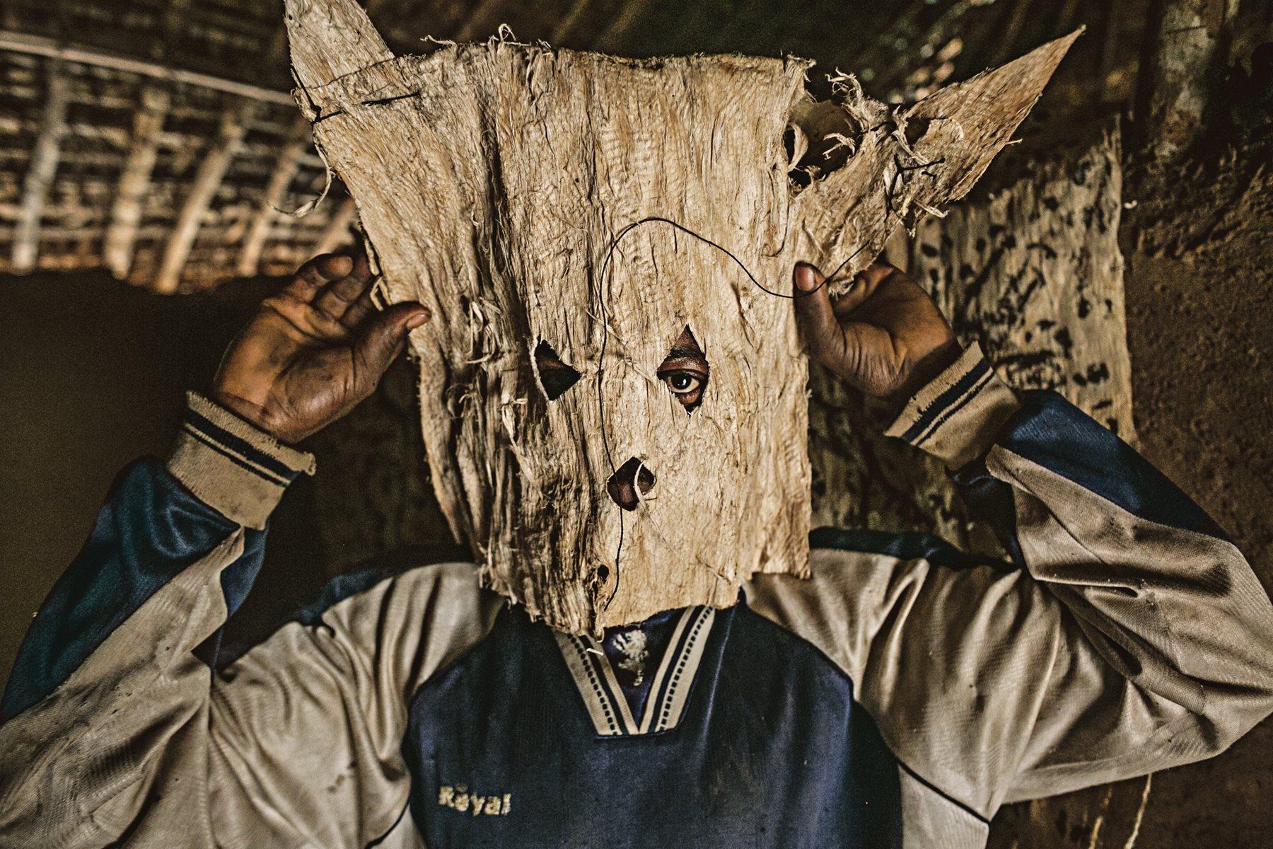 Un cazador de una aldea de la República Democrática del Congo (RDC) se ajusta la máscara que llevará durante la partida
