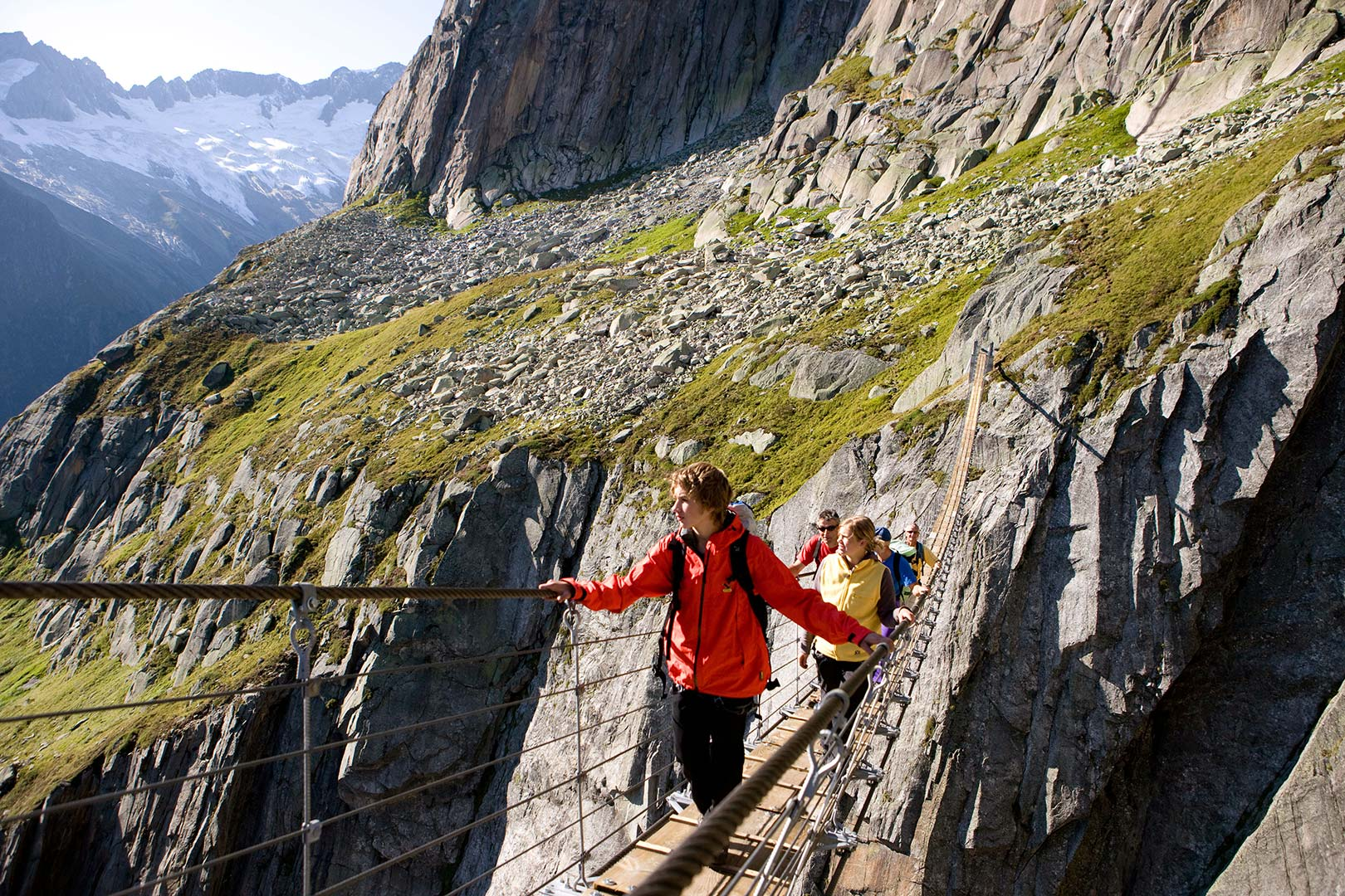 Picture of hikers crossing the Göscheneralp Salbitbrücke suspension bridge, Canton Uri, Switzerland
