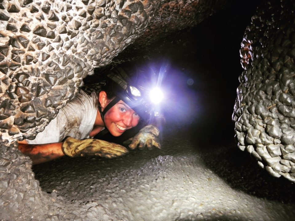 Riley crawls through the Brain Drain in Jewel Cave