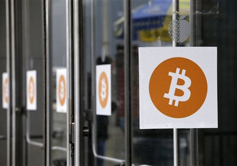 Bitcoin logos are displayed at the Inside Bitcoins conference and trade show, Monday, April 7, 2014 in New York