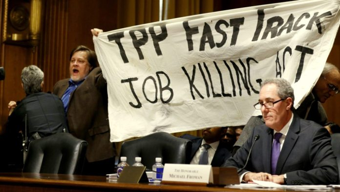 """A policewoman removes a man protesting the Trans-Pacific Partnership (TPP) as U.S. Trade Representative Michael Froman (R) testifies before a Senate Finance Committee hearing on """"President Obama's 2015 Trade Policy Agenda"""" on Capitol Hill in Washington January 27, 2015. The top U.S. trade official urged Congress to back the administration's trade agenda on Tuesday and said an ambitious Pacific trade pact is nearing completion. Froman said the administration looked to lawmakers to pass bipartisan legislation allowing a streamlined approval process for trade deals, such as the 12-nation Trans-Pacific Partnership. REUTERS/Kevin Lamarque (UNITED STATES - Tags: POLITICS BUSINESS CIVIL UNREST)"""