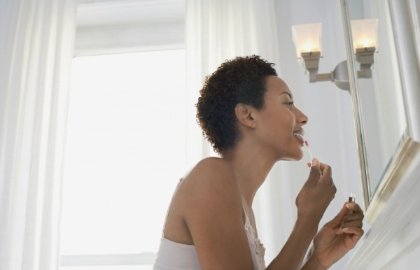 Side view of an African American woman applying lip gloss in mirror at home