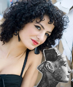 Modern beautiful woman with dark curly hair and Queen Nefertiti statue