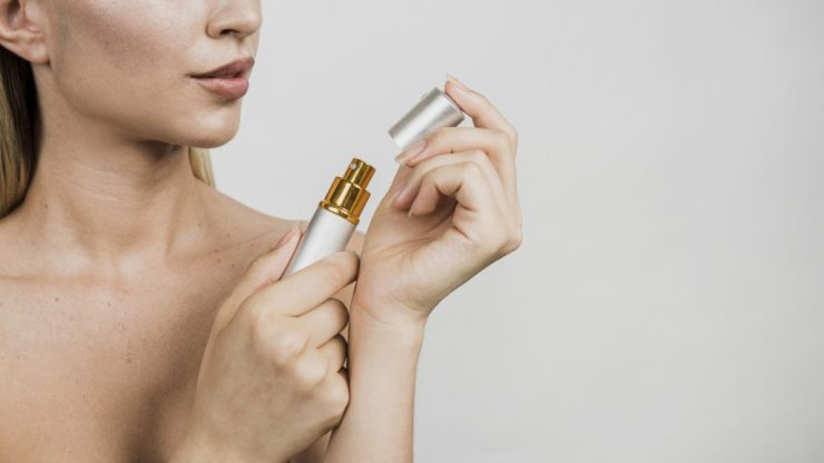 Donna che stappa boccetta di profumo