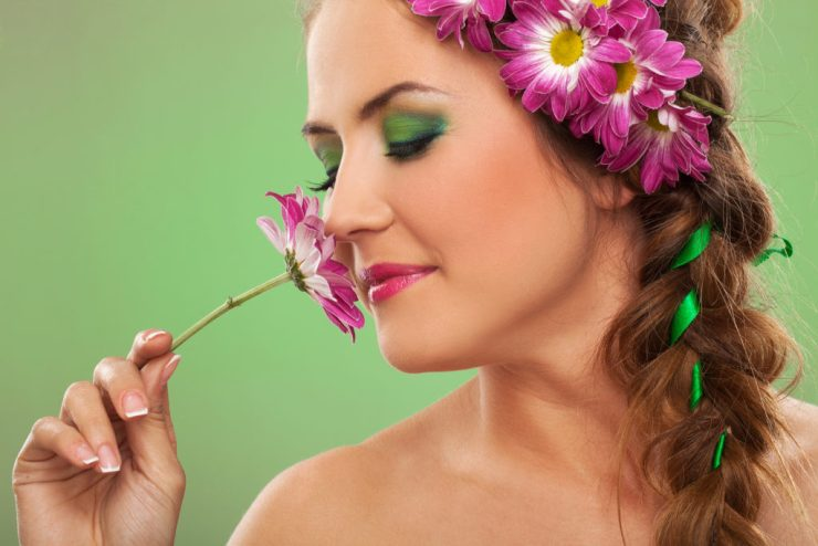 Young beautiful woman with expressive makeup sniffing flower