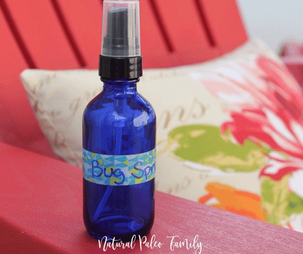 homemade bug spray in a blue spray bottle on the arm of a red Adirondack chair