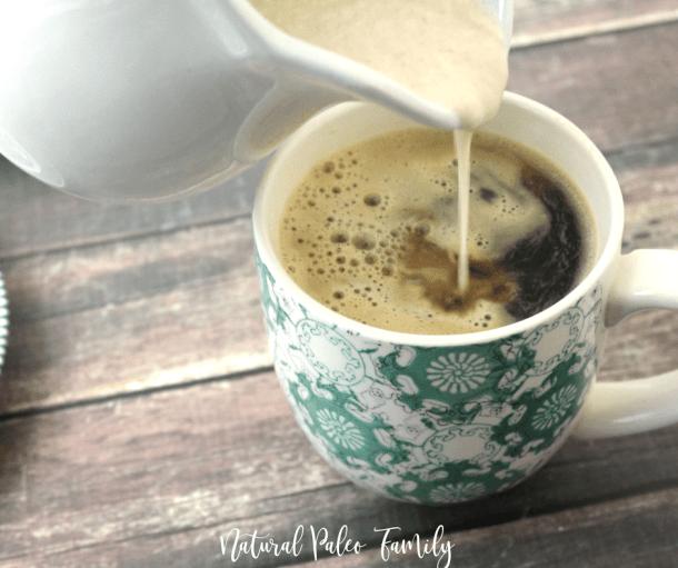 white ceramic pitcher pouring paleo pumpkin spice latte into a coffee mug
