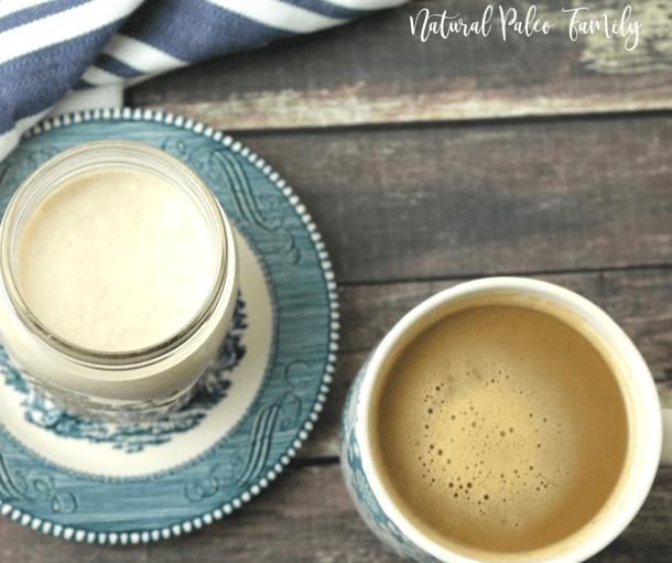 coffee mug with paleo pumpkin spice latte next to a glass jar of milk