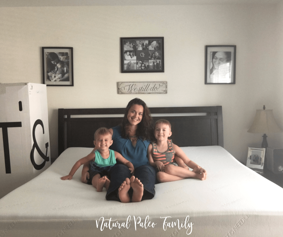 woman and two young boys sitting on a mattress smiling at the camera