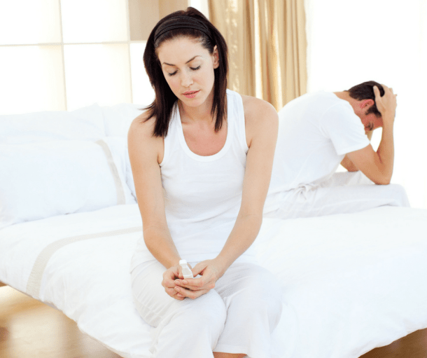 sad woman sitting on bed, holding pregnancy test, surviving infertility