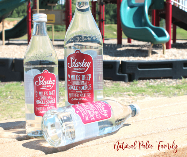 three Starkey spring water bottles on a bench in front of a playground