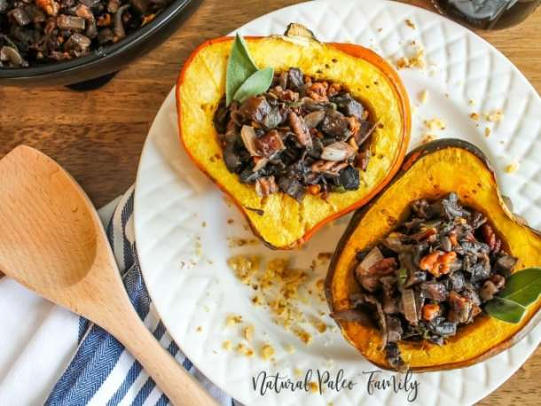 two mushroom stuffed acorn squash on a white plate