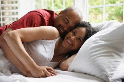 Smiling Black couple laying in bed --- Image by © LWA/Dann Tardif/Blend Images/Corbis