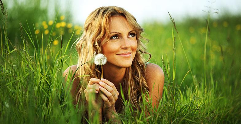 femme allongée dans l'herbe avec un pissenlit dans les mains. Elle est détendue, zen, apaisée et sourit pour manifester son bien-être
