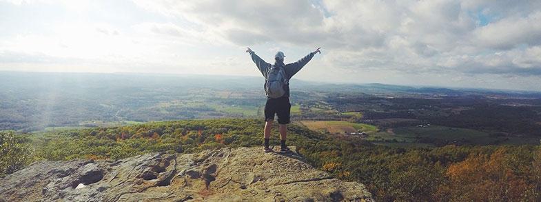 Homme au sommet d'une colline, motivé à l'idée de trouver comment arrêter de boire et stopper sa dépendance à l'alcool