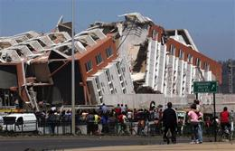 Residents look at a collapsed building in Concepcion, Chile, Saturday Feb. 27, 2010