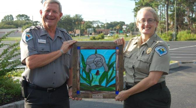 Volunteer and CSO Board member, Nills Anderson presents his stained glass portrait of Rosie, the manatee to Park Manager Kimberlee Tennille.