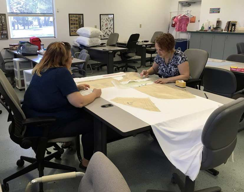 Pam Phelps and Faith Peix work on altering a pattern.