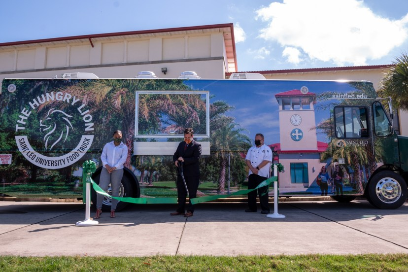 Saint Leo University President Jeffrey Senese (center), alongside Student Government Union President Ashley Butler (left) and Director of Dining Services Justin Bush (right), cut the ribbon signifying the opening of The Hungry Lion food truck.