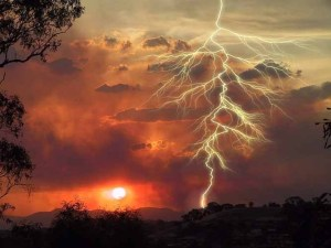 A NASA photograph showing a lightning bolt at sunset over a line of trees.