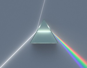 A photograph showing a dispersive glass prism splitting a ray of pure white light into its colour components.