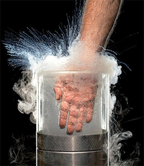 A photograph showing the Leidenfrost effect of liquid nitrogen in action. The experimenter's warm hand is seen plunged into a vat of liquid nitrogen, which spills over. Don't Try This At Home!