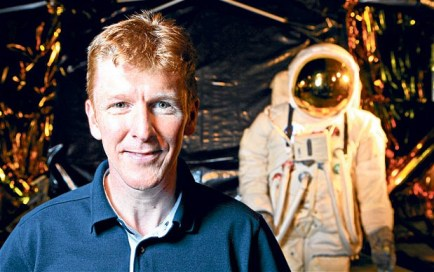 A photograph of Major Tim Peake posing in front of his pressure suit.