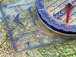 A close-up photograph showing a map and a compass.