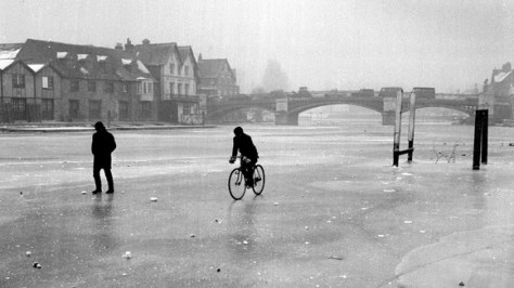 A 1963 black and white photograph of the 'Big Freeze'. A man can be seen walking and another one cycling on the frozen River Thames.