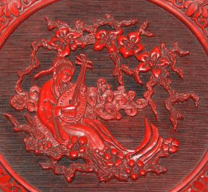 A photograph showing a Chinese cinnabar plate showing a woman playing a plucked string musical instrument.