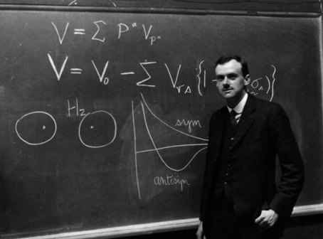 A black and white photograph showing Paul Dirac standing in front of a blackboard covered with equations.